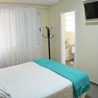 Destaque para a entrada do banheiro da suíte do Flat Alexandrina 3 quartos da Pousada dos Sonhos, com televisão tela plana afixada na parede em frente a cama.