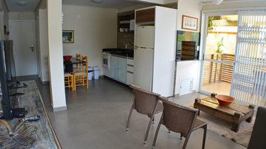 Sala de estar e cozinha completa do flat Alexandrina 3 quartos da Pousada dos Sonhos. O flat conta com uma área externa privativa com cadeiras, aumentando a área útil da acomodação.